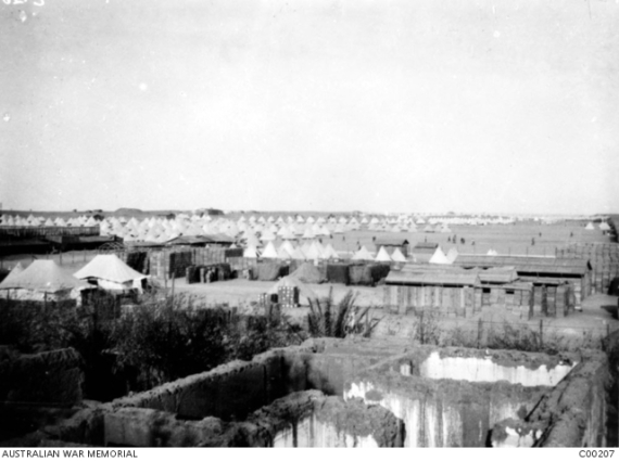 Tel el Kebir camp between Cairo and the Suez Canal. Australian troops came here after the evacuation of the Gallipoli peninsula; here the organisation of the 4th and 5th Divisions began in February 1916. In the foreground is a roofless, possibly ruined house with a garden. Stores are piled beyond; on the left are two large tents and beyond is a sea of Eight Person Indian Production (EPIP) tents used for accommodation.